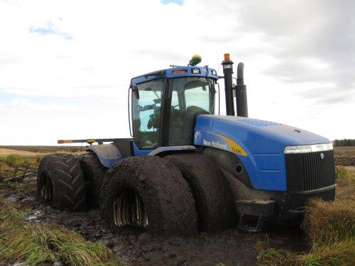 Foto van een New Holland TJ 380, bezig met vast zitten.  zo blijkt maar weer, een knik trekker kan ook vast komen te zitten:P haha