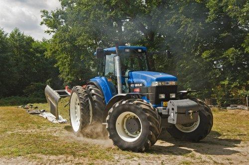 Foto van een New Holland 8870 A, bezig met gras inkuilen. Het mag van mij morgen wel weer zomer zijn...