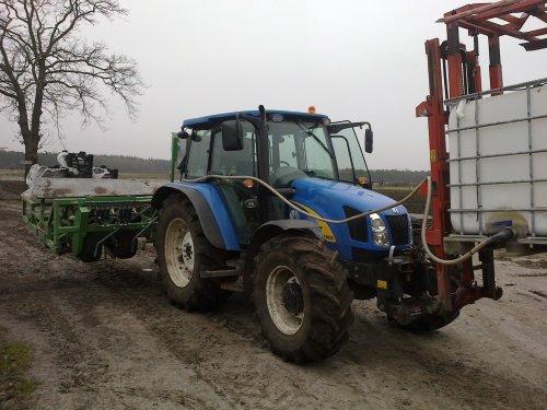 Foto van een New Holland T 5050 met basrijs 6 rijen aardbeienplant machine, bezig met poseren. eerste planten van 2013 zitten er weer in