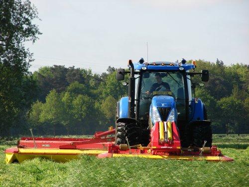 Foto van een New Holland T 6070 Gen2, bezig met gras maaien.   t laatste snippertje gras er nog even af