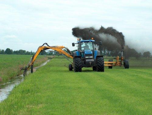 Foto van een New Holland TM 175, bezig met poseren.lekker een beetje bagger pompen op een mooie zomer dag.
