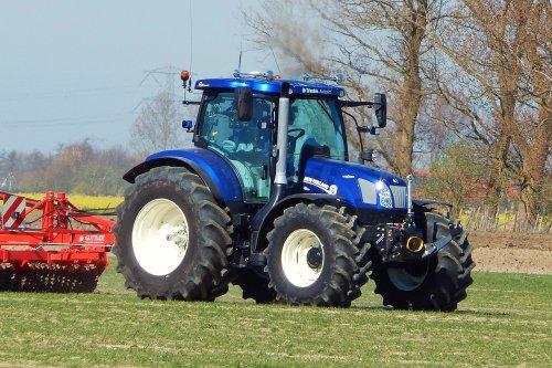 Foto van een New Holland T 6.160, bezig met ploegen / eggen. Kun je van een relatief lichte trekker iets stoers maken?  Ja hoor, kijk maar naar deze T6 Bluepower!