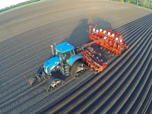 Foto van een New Holland T 8050 met Grimme 8 rijige poter aardappelen aan het poten.. Geplaatst door FerreV op 05-04-2014 om 20:56:03, met 4 reacties.