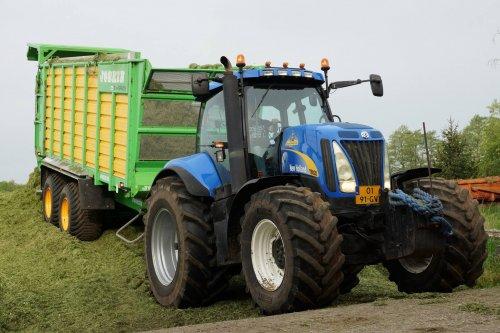 Foto van een New Holland T 8020, bezig met gras inkuilen.   nh+joskin silo-space 20/40 aan het inkuilen, 2e dag met de nieuwe hakselaar ipv de 'oude' FX450