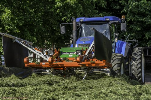 Foto van een New Holland T 7550, bezig met gras inkuilen.  loonbedrijf De Weer uit Bornerbroek aan het grashakselen