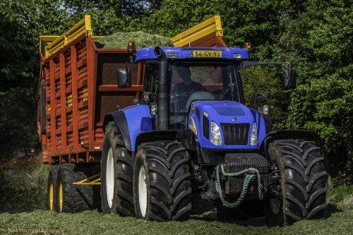 Foto van een New Holland T 7550, bezig met gras hakselen.  loonbedrijf De Weer uit Bornerbroek aan het grashakselen