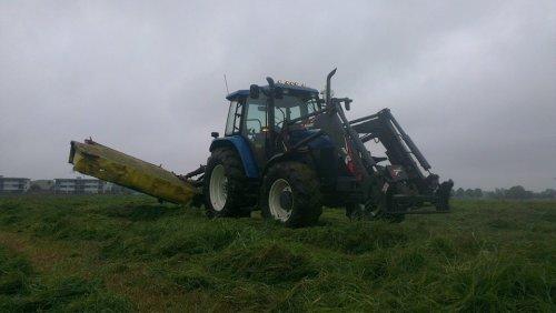 Foto van een New Holland TS 90, druk bezig met gras maaien. Geplaatst door newholland- op 24-07-2014 om 09:06:31, met 4 reacties.