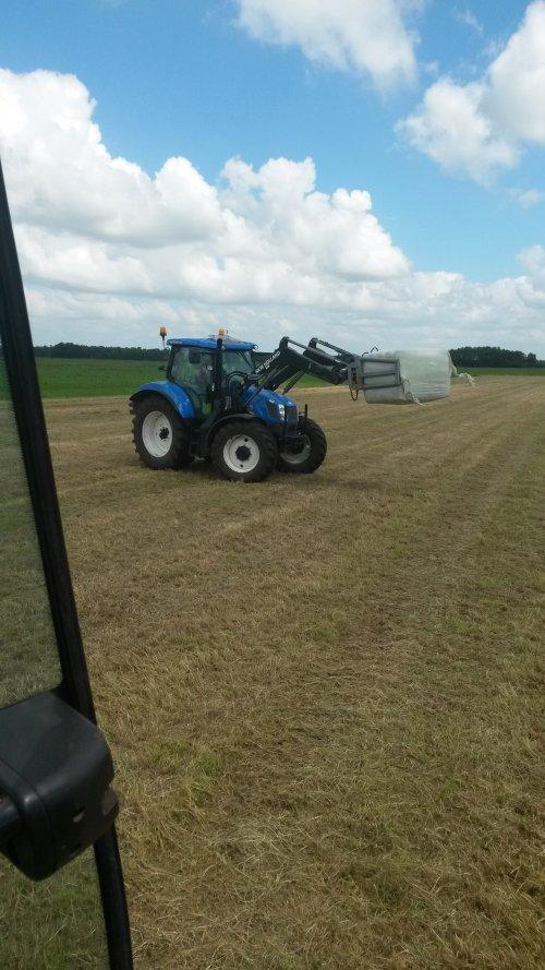Foto van een New Holland T 6.120, druk bezig met Balen halen.. Geplaatst door vudwifiattm op 25-08-2014 om 22:15:06, op TractorFan.nl - de nummer 1 tractor foto website.