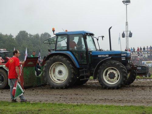 Foto van een New Holland 8340, bezig met tractorpulling. Bij tractorpulling Almkerk 2014 (thuiswedstrijd)