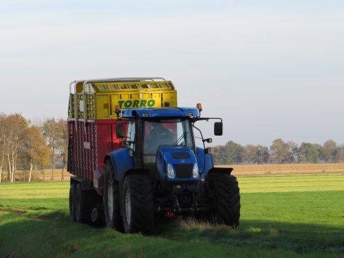 Foto van een New Holland T 7520, bezig met gras inkuilen. 28-10-2014. Geplaatst door oldtimergek op 29-10-2014 om 23:27:01, op TractorFan.nl - de nummer 1 tractor foto website.