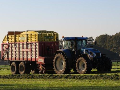 Foto van een New Holland T 7520, bezig met gras inkuilen. 28-10-2014. Geplaatst door oldtimergek op 29-10-2014 om 23:27:03, op TractorFan.nl - de nummer 1 tractor foto website.