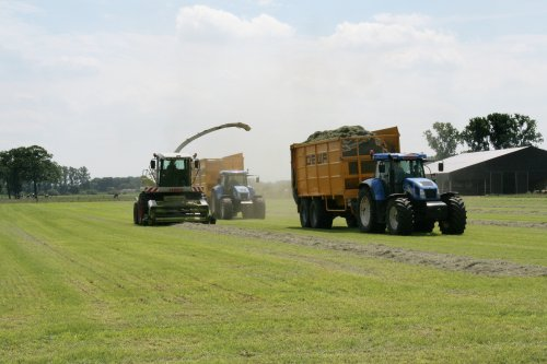 Foto van een New Holland Meerdere, bezig met gras hakselen. Op de foto loonbedrijf Chris Mols met TVT 195 en T7550, foto is vorige zomer genomen.