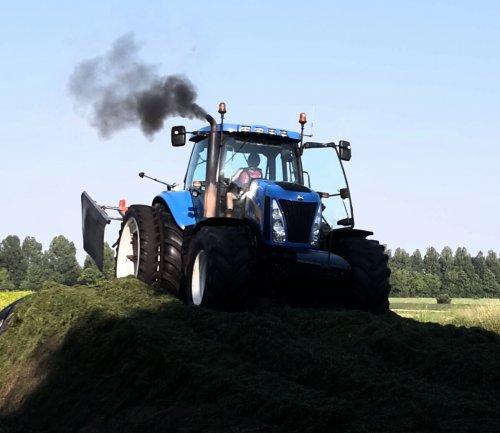 Foto van een New Holland T 8030, druk bezig met Gras inkuilen.. Geplaatst door hoffie306 op 06-08-2015 om 19:00:07, op TractorFan.nl - de nummer 1 tractor foto website.