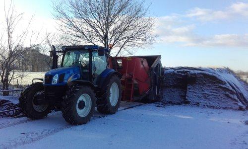 Foto van een New Holland T 6010 Delta met Trioliet voermengwagen, bezig met voer pakken in de sneeuw