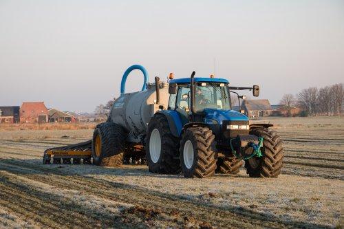 Loonbedrijf Maurice Land aan het grasland bemesten met hun hun New Holland TM140 met Slootsmid tank met daarachter een Veenhuis bemester.  Meer foto's zijn te bekijken op: http://www.trekkerfotografie.nl