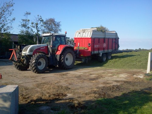 Foto van een Steyr CVT 6135, bezig met gras inkuilen. gras kuilen met steyr 6135 cvt en lely tigo 50r