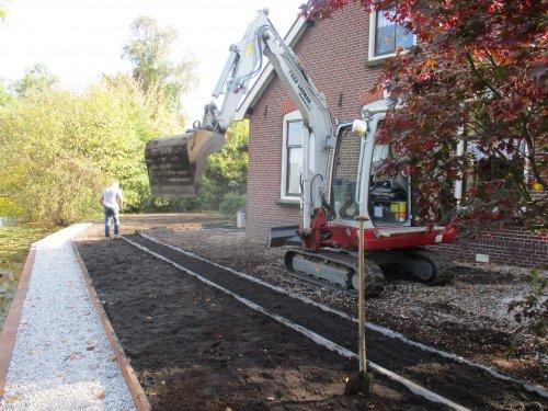 Takeuchi TB 235 van Loonbedrijf Fred Looman bezig met tuin aanleggen. Beschoeiing en plantvakken heeft Fred Looman aangelegd. Nu zelf nog beplanten en gazon nog egaliseren en inzaaien
