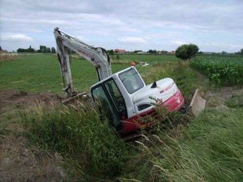 Foto van een Takeuchi TB 285, bezig met vast zitten. Vergeten planken over de gracht te leggen :). Geplaatst door mathias vb op 17-07-2015 om 17:12:16, op TractorFan.nl - de nummer 1 tractor foto website.