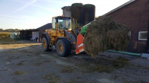 Foto van een Volvo L70E met een bakje gras klaar om de mengwagen weer te vullen tijdens het mengkuilmaken.