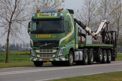 """Persfoto van een Volvo FH 4th gen, opgebouwd als open laadbak.  Expeditiebedrijf Lodder B.V. heeft onlangs drie Volvo's FH 460 6x4 luchtgeveerde trekkers in gebruik genomen. Alle drie Volvo FH-trekkers zijn voorzien van radiografische afstandsbediening. De aflevering is gedaan door Volvo Group Truck Center Zoetermeer. Expeditiebedrijf Lodder is gespecialiseerd in het transport van alles wat met de bouw te maken heeft. De nieuwe trucks komen ter vervanging in het bestaande wagenpark, waarin Volvo inmiddels goed is vertegenwoordigd. Directeur Wim Sjouw: """"Deze Volvo's worden door ons ingezet voor het dagelijkse vervoer van rijplaten en draglineschotten door heel Nederland voor onze klant Plaisier uit Hendrik-Ido-Ambacht. We hebben bij de aanschaf vooral gekeken naar de veiligheidsaspecten voor onze mensen. Zij hebben op de plaatsen waar ze hun werk moeten doen, nogal eens te maken met onoverzichtelijke en gevaarlijke situaties, zeker wanneer het slechter weer is."""" Wim Sjouw vervolgt: """"Door toepassing van radiografische afstandsbediening hebben we hier een ideale oplossing voor. Onze mensen kunnen nu veel sneller, veiliger en overzichtelijker werken. Ze hoeven bovendien veel minder naar voren te lopen. Sterker nog, de trucks zijn uitgerust met sensoren aan de voorzijde van de cabine, die meten of er niets in de weg staat en in het uiterste geval zorgen voor een noodstop. Door de sensoren kunnen de chauffeurs ook vanaf de plaats van de kraanbediening veilig werken. Werksituaties worden overzichtelijker en daardoor ook minder belastend. We zijn zuinig op onze mensen, het zijn uiteindelijk de mensen die het werk uitvoeren."""" De trucks hebben een RVS kastenwand met een geïntegreerde hydrauliek tank achter de cabine. De opbouw van de nieuwe Volvo's met de hydrauliek installatie en het radiografische gedeelte is compleet verzorgd door het werkplaatsteam van Volvo Group Truck Center Zoetermeer, dat daarbij ondersteuning heeft gekregen van VDA uit Zoeterwoude. Bij de realisatie """
