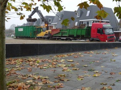Foto van een Volvo Kraan. Mensink bosbouw aan het overladen. Met truck en kleine container de wijk in. Wanneer de bak vol is overladen in de grote.