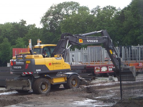 Foto van een Volvo EW 180D, bezig met dumperen.  Afgelopen week is gestart met de realisatie van fase 1 van de uitbreiding van het terrein van Geert-Jan de Kok in Esbeek. Dit is alweer heel wat jaartjes geleden aangekocht nadat de steenfabriek zijn deuren sloot en het terrein in delen aan andere bedrijven werdt verkocht. Fase 2, een stuk achter de betonnen wand(tot aan de sloot) links buiten beeld wordt later erbij gevoegd, maar blijft voorlopig nog bij het terrein van Reyrink Diessen.