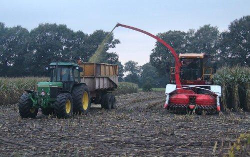 Foto van een Vredo VT 3326 van Firma Aanstoot-Pekkeriet uit Holten, bezig met maïs hakselen met Champion 3000 van Kemper ervoor Foto gemaakt in Holten net voor in val van de duister op 14-10-2013 Er naast rijdt een John Deere 3650 met Veenhuis kipper