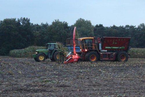 Foto van een Vredo VT 3326, bezig met maïs hakselen met Champion 3000 ervoor. Ernaast rijdt John Deere 6810 met Veenhuis kipper met schoten erop